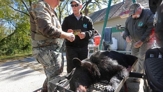 Wildlife tech Kim Tinnes speaks to a hunter at the weigh station in Fredon on Monday, the first day of New Jersey's black bear bow and arrow hunt.