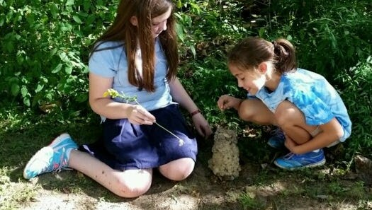 Laynie Wollam and Aubrey Gehring fish down the chimney of a crawfish hole.
