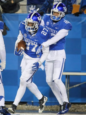 Kentucky safety Mike Edwards is congratulated by Kentucky cornerback Jared Tucker after Edwards scored a touchdown during the second half of an NCAA college football game against Charlotte, Saturday, Nov. 21, 2015, in Lexington, Ky. Kentucky won 58-10.