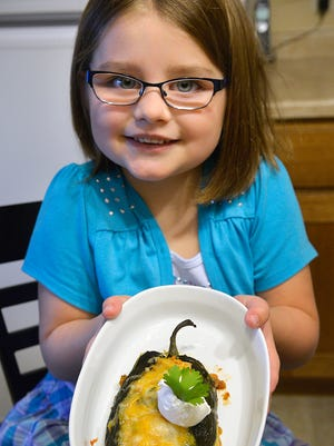 Kaitlyn Reichel, 6, poses Monday, Oct. 26 with the stuffed Poblano pepper recipe she and her mother, Cindy, Sartell, have entered in an Uncle Ben's rice contest. If they are one of the five winners, Kaitlyn's elementary school would receive a cafeteria makeover and her family would get $15,000.