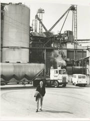 A photograph taken around 1965 shows Frank Perdue of Perdue Farms Inc., standing in front of his grain storage tanks near Salisbury, Maryland.