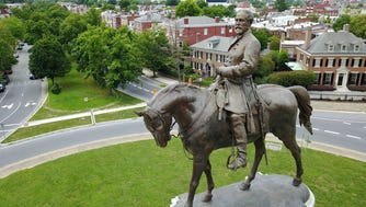 A statue of Confederate Gen. Robert E. Lee stands in the middle of a traffic circle on Monument Avenue in Richmond, Va., in this June file photo.