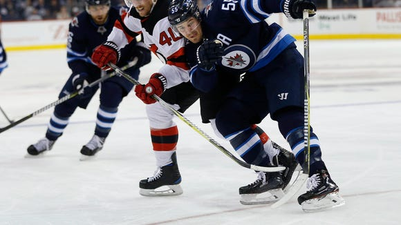 New Jersey Devils' Blake Coleman (40) and Winnipeg Jets' Mark Scheifele (55) fight for possession of a loose puck during the second period of an NHL hockey game in Winnipeg, Manitoba, Saturday, Nov. 18, 2017. (John Woods/The Canadian Press via AP)