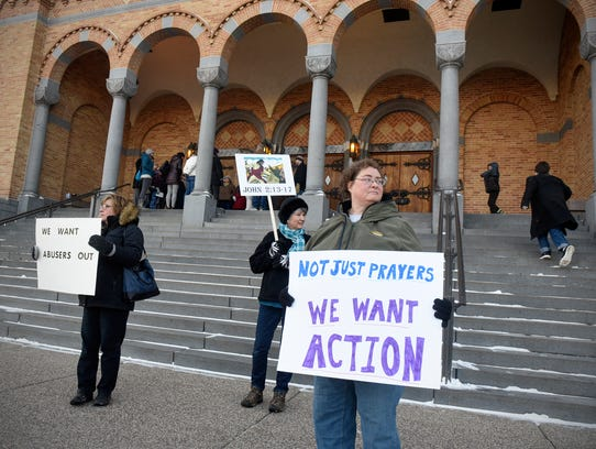 People hold signs outside St. Mary's Cathedral before