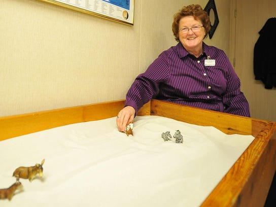 Dr. Mary Hennessy rearranges the animal toys on her