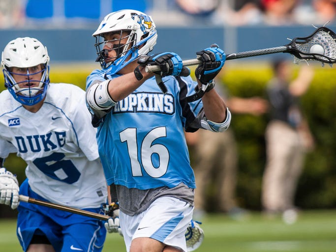 Johns Hopkins' Connor Reed (No. 16) puts a shot on goal in front of Duke's Will Haus (No. 6) in the first quarter of an NCAA Tournament quarterfinal game between Duke and Johns Hopkins at Delaware Stadium in Newark on Sunday afternoon, May 18, 2014. Duke derated Johns Hopkins 19-11.