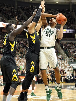 Feb 11, 2017; East Lansing, MI, USA; Michigan State Spartans forward Nick Ward is defended by Iowa Hawkeyes forward Tyler Cook, center, and guard Peter Jok in the second half at the Jack Breslin Student Events Center.
