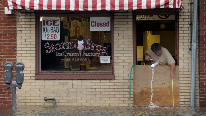 Sveinn Storm, owner of Storm Bros. Ice Cream Factory, measures the floodwaters outside his store in Annapolis, Md., on Oct. 30, 2012, in the aftermath of Superstorm Sandy.