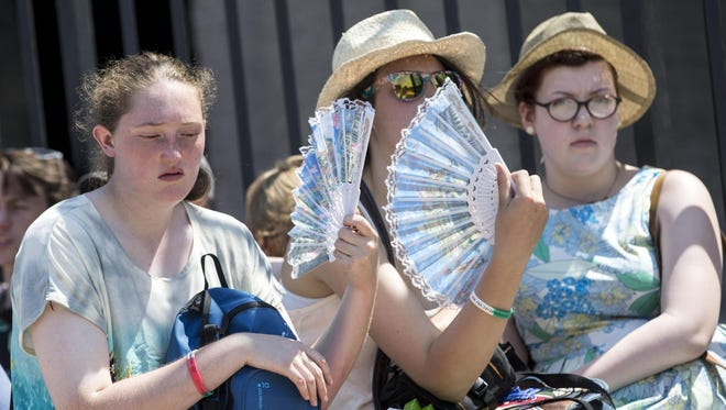 Tourists cool off with a fan in Rome on July 4, 2015, during a heat wave  Much of Europe endured an extremely warm month.