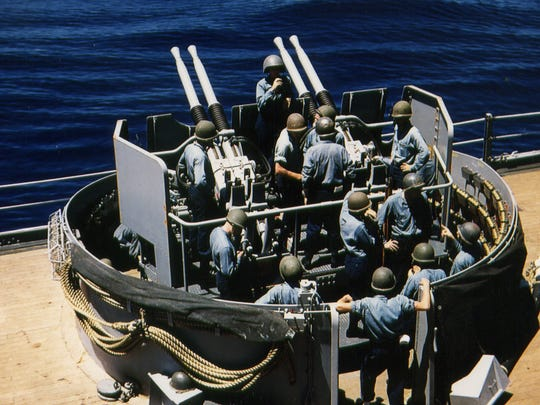 Sailors aboard the Batlteship New Jersey  man the four barrels of a Quad 40 anti-aircraft  gun inside a protective steel tub about 70 years ago
