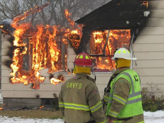 Firefighters watch as a home is burned Dec. 13, 2014,