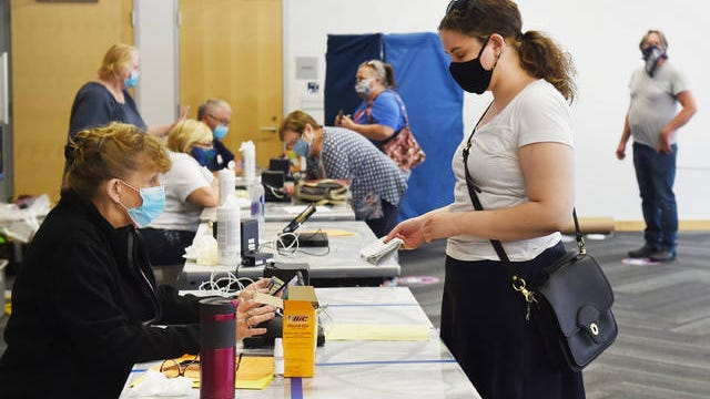 Poll-worker Laurie Shinn helps Emily Bickel before casting her vote in the primary election at Ames Public Library Tuesday, June 2, 2020, in Ames, Iowa. Photo by Nirmalendu Majumdar