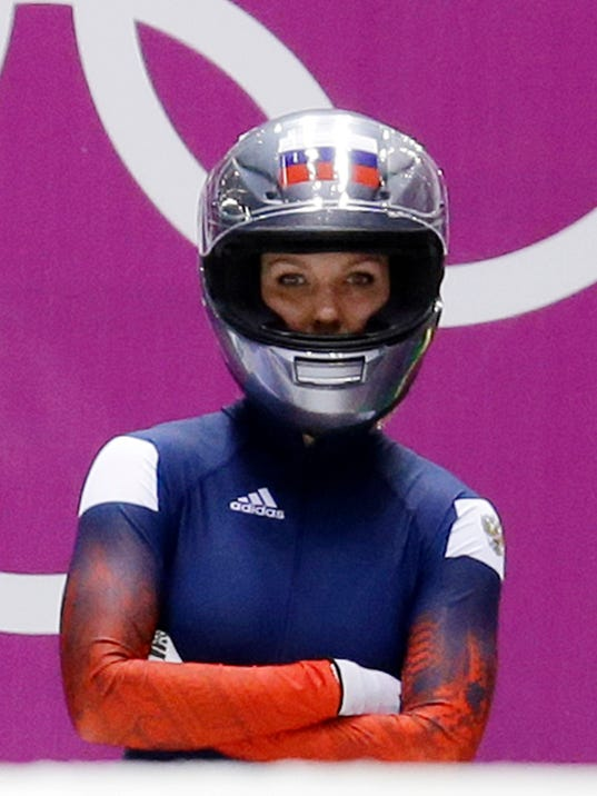 "FILE - In this Feb. 18, 2014 file photo, Nadezhda Sergeeva, of Russia, prepares for the first run during the women's two-man bobsled competition at the 2014 Winter Olympics, in Krasnaya Polyana, Russia. Sergeeva's bobsled training outfit says a lot about what life will be like for an ""Olympic Athlete from Russia."" There is an old, anonymous black race suit with tape over several logos. Underneath, a white T-shirt with a simple message - ""I Don't Do Doping."" As punishment for doping offenses at the 2014 Sochi Games, the International Olympic Committee has forced Russian athletes competing in Pyeongchang to do so as OARs in neutral uniforms and with no national insignia.  (AP Photo/Natacha Pisarenko, File)"