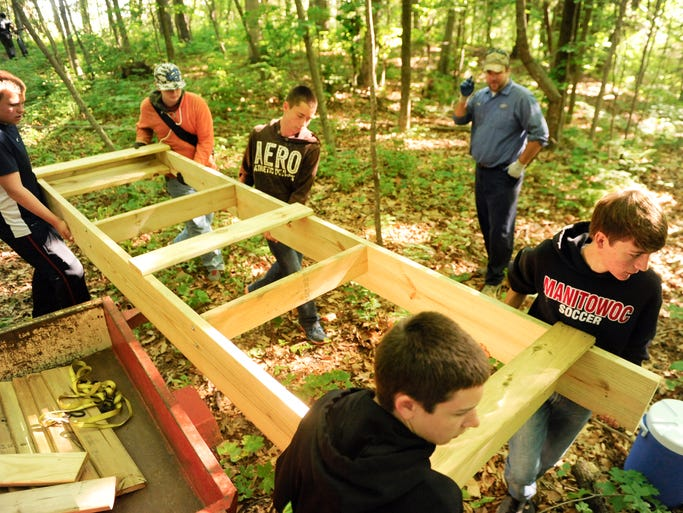 Students from left, David Knox, Collin Hlinak, Nick Hodgson, Samual Evanoff and Gabe Barden carry a 12-foot section of boardwalk that will become part of the 48-foot long boardwalk on the multi-use recreational trail at Camp Vits during the summer community service class through the Manitowoc Public School District on Thursday. Sue Pischke/HTR Media. Photo taken on Thursday, July 17, 2014.