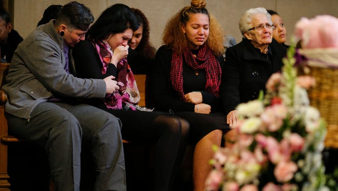 Amber Caudell, center, is hugged by Nick Caudell as Alexandrea's sister, Avalynn, center right, and a relative mourn at the funeral, Saturday, Jan. 28, 2017, at Spring Grove Cemetery. Alexandrea, 9, was killed after she was shot along with her father, Alex, Jan. 18. in Mount Auburn, police said. Her father struggled with a gunman who had stormed into their Mount Auburn house, her aunt told The Enquirer.