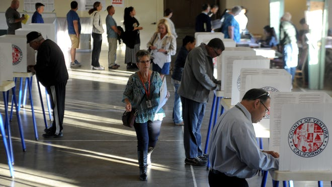 Stephen Frantela, right, votes early in the morning before work at Grace Lutheran Church in Ventura.
