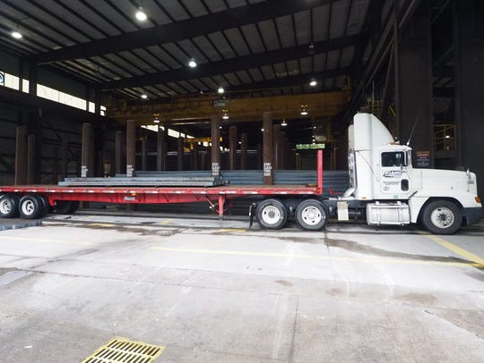 A truck carrying steel sits at the loading dock at