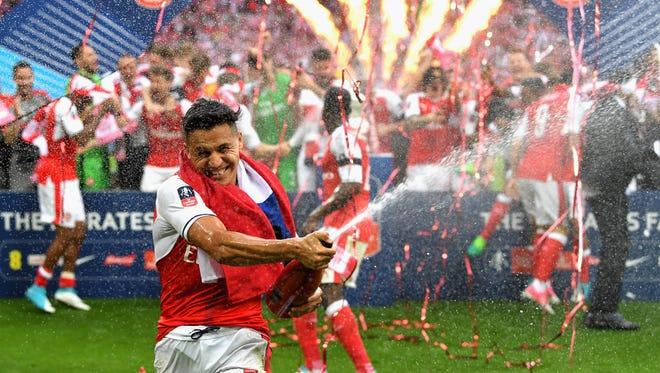 Arsenal's Alexis Sanchez sprays champagne in celebration.