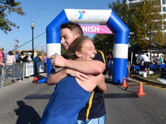 Tara Dawson and Adam Devery embrace after crossing