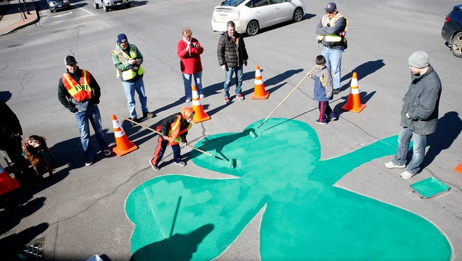 Horseheads Fire Department crews and community members paint a large shamrock in Hanover Square Sunday afternoon.