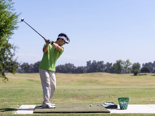 David Kwon of Visalia practices on the driving range at Valley Oaks Golf Course.