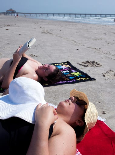 Haley Turpin (left) reads to Krystal Duran on the beach in Port Aransas while the women from Houston visit the city for a long girls' weekend on Sunday, March 4, 2018. Six months after Hurricane Harvey hit, the tourist town is readying for their tourist season. The category four hurricane damaged 95 percent of businesses and 75 percent of the city's homes suffered critical damage or were destroyed.