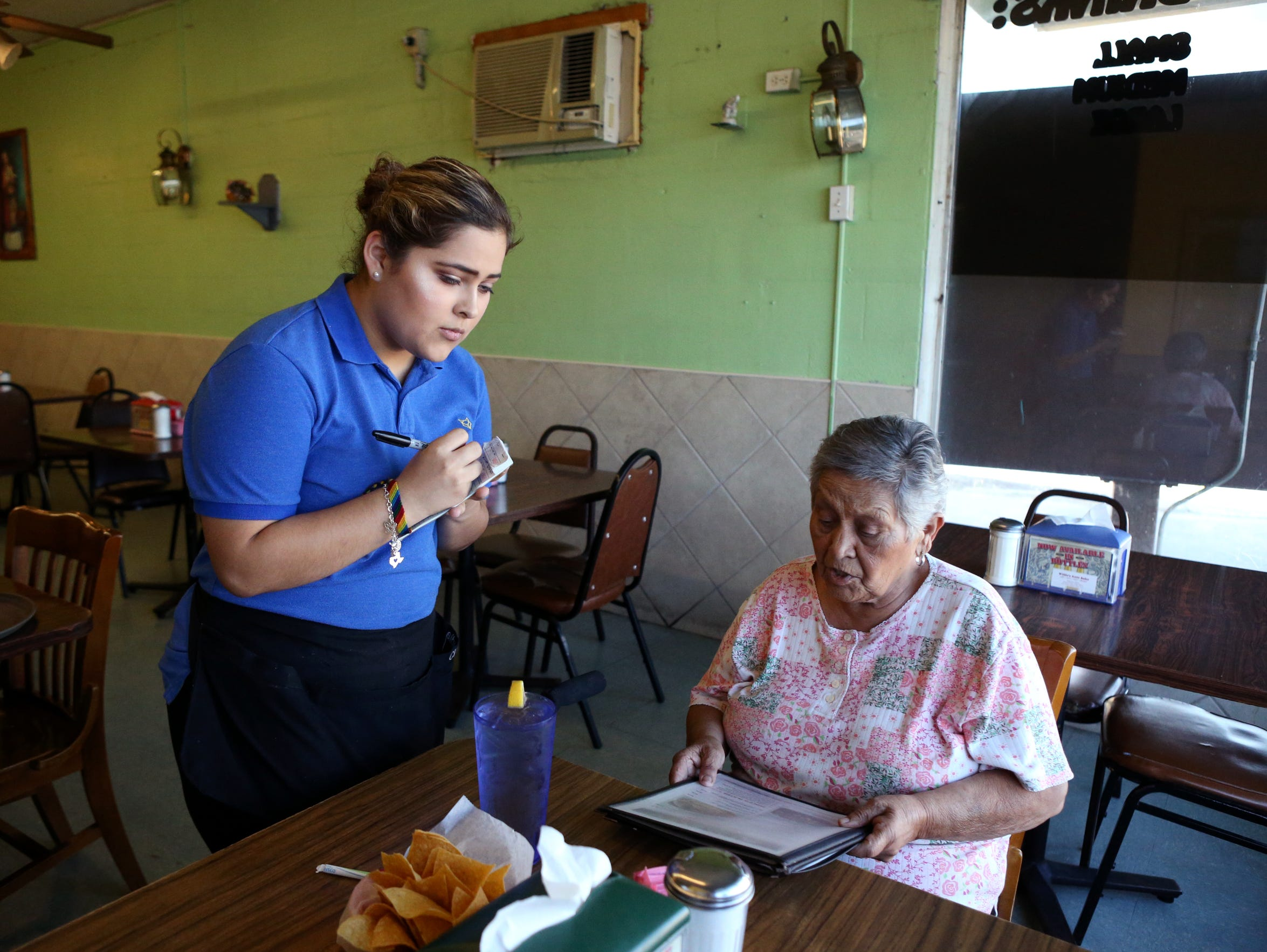 Claudia Jimenez, 19, takes an order from Lupe Muñoz at work on October 18, 2017. She wonders what her life would have been like if she had instead grown up in Jalisco, Mexico, where she was born.