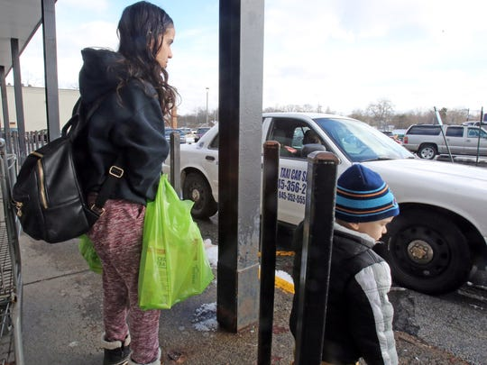 Ashlee Delgado waits for a cab to take her home after grocery shopping with her son, Carmelo Monge, in Spring Valley, N.Y., on Feb. 8, 2018. Delgado's registration had been suspended over unpaid tolls on the Gov. Mario M. Cuomo Bridge. To clear the suspension, she had to pay $1,548 - towing, storage, DMV fines, tickets, defensive driving class - and that didn't include the $3,500 in violations.