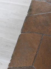 Paver stones butt up against the wood flooring in the