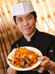 Chef Chen displays a serving of nian nian you yu or