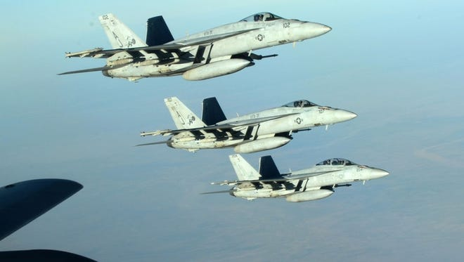In this Tuesday, Sept. 23, 2014 photo released by the U.S. Air Force, a formation of U.S. Navy F-18E Super Hornets leaves after receiving fuel from a KC-135 Stratotanker over northern Iraq as part of U.S. led coalition airstrikes on the Islamic State group and other targets in Syria.