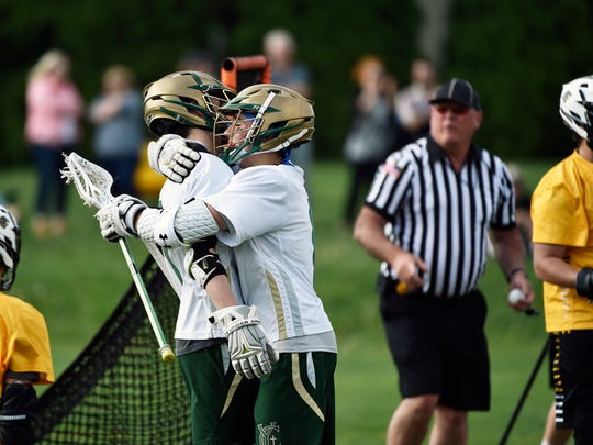York Catholic's Dimitri Amalfitano, left, is greeted by Ian Schlough after scoring against Red Lion in the first half of a YAIAA boys' lacrosse game Thursday, April 27, 2017, at York Catholic. York Catholic defeated Red Lion 13-12.