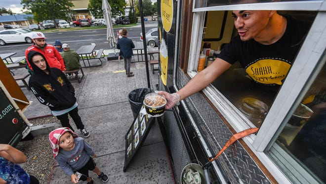 Daniel Arellano serves up an order from the Cupbop food truck during a recent visit to the Soho Food Park in Holladay Utah on Sept. 22, 2016. Food truck owners often need to navigate confusing governmental hoops and regulations just to serve food to hungry eaters.