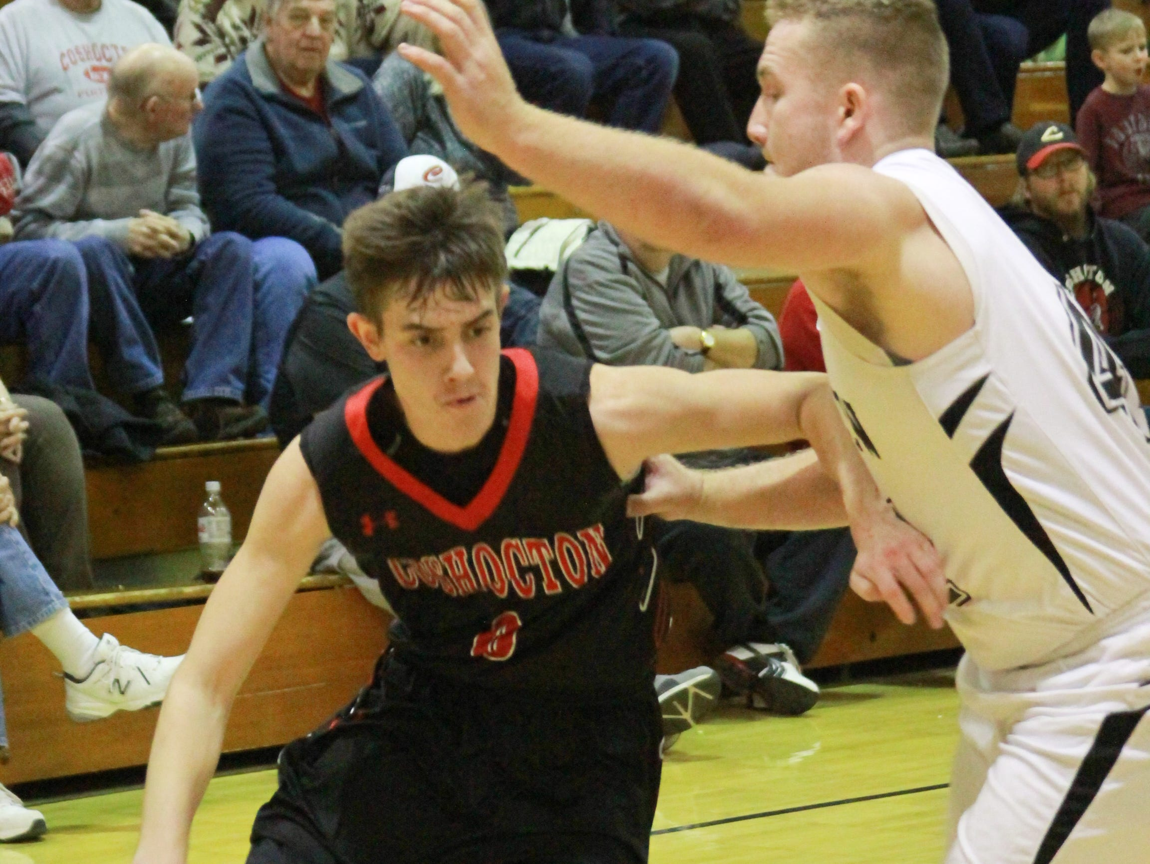 Coshocton's Ashton Jarvis drives on Trevor Wine Tuesday night.