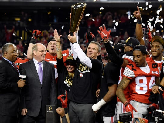 Urban Meyer holds up the trophy after Ohio State beat