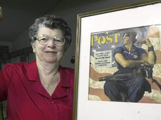 """In this May 22, 2002. file photo, Mary Doyle Keefe poses at her home in Nashua, N.H., with the May 29, 1943, cover of the Saturday Evening Post for which she had modeled as """"Rosie the Riveter"""" in a Norman Rockwell painting."""