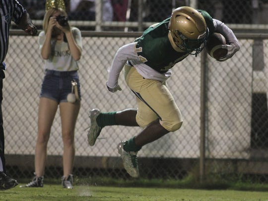 Lincoln receiver Derek Curry flies through the air while escaping a tackle to score his second touchdown of the first half against Chiles.
