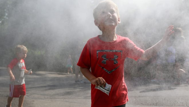 Cooper Clare, 4, of Edgewood cools off in front of the mister at the Cincinnati Zoo & Botanical Garden. In the background is his brother, Chase, 3. The high Monday was 87 degrees, but the humidity made it feel even hotter. Highs in the upper 80s and lows in the mid 60s are in the forecast through Friday.