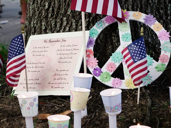 Candles, American flags and other momentos are left