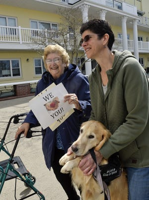 """Nancy Bishop, right, and her mother, Mary, watch her father from outside Royal Megansett in North Falmouth in March shortly after visits were banned at nursing homes statewide amid the coronavirus pandemic. Her father, Al, died in May, and Bishop believes it was from """"a broken heart"""" because he could not bear the separation from family. Nursing homes are slowly preparing to admit visitors again."""