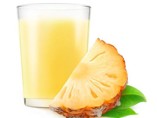 Glass of pineapple milkshake isolated on white background