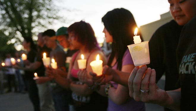 Participants in the 2012 Take Back the Night rally observe a moment of silence outside the Farmington Civic Center.