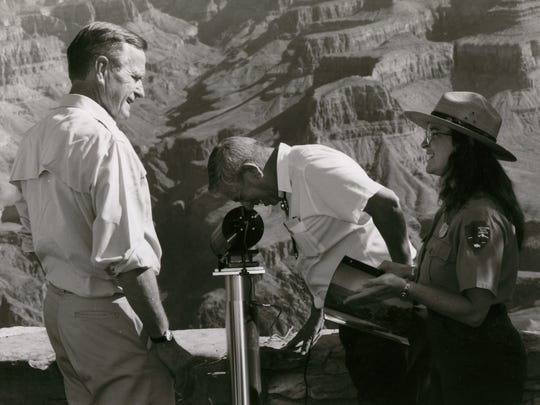 Former President George H. W. Bush gets an explanation of some of the equipment used to monitor air quality in the Grand Canyon from Park Service geologist Linda Mazzu as Interior Secretary Manuel Lujan peers through the instrument on September 19, 1991.