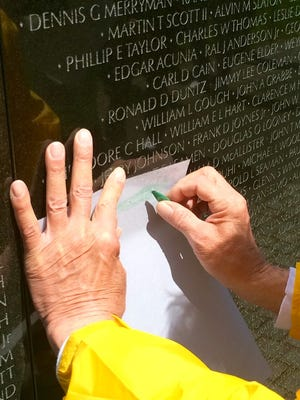 Dan Reid of Schofield makes an etching of of the name of Michael P. Malueg on the Vietnam Veterans Memorial in Washington D.C. as part of Never Forgotten Honor Flight.