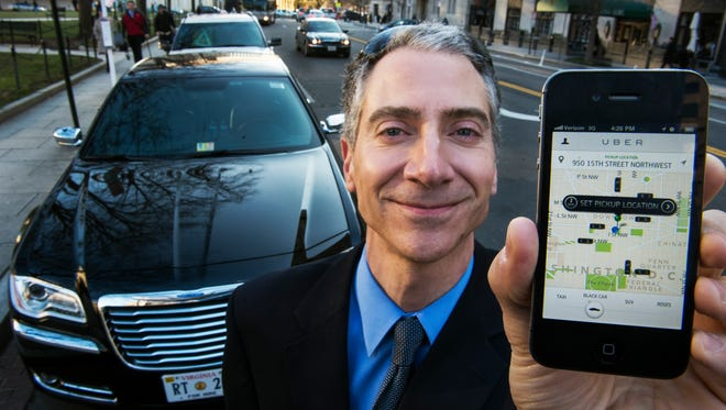 Peter Faris, CEO of Szabo Faris LLC Transportation Solutions, stands in front of one of his vehicles while holding a smart phone with the Uber app that orders up his sedan service  February 14, 2013 in Washington, DC.