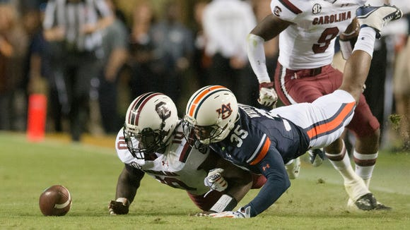 Auburn defensive back Jermaine Whitehead fights for the ball as South Carolina linebacker Skai Moore recovers the onside kick during Saturday's game.
