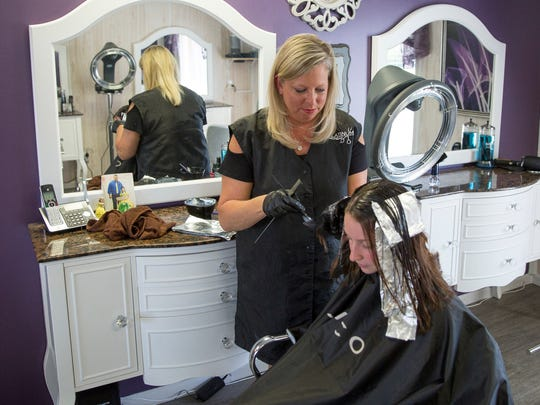 Melissa Hiatt, the owenr of Platinum Salon & Massage, works with a client in her store on May 18. The store offers a wide variety of styling and massage needs.