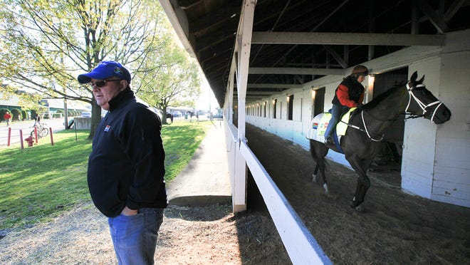 Trainer Mike de Kock waits outside the barn at Churchill Downs as exercise rider Lisa Moncrieff prepares to bring Mubtaahij, who won the UAE Derby, to the race track. April 28, 2015
