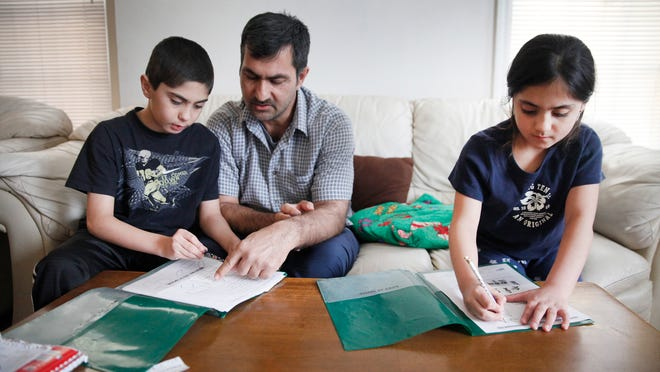 """Aziz Sharifi, center, helps his children Khaybar Sharifi, 10, left, and Dewah Sharifi, 7, with their homework after school in their Corn Hill apartment. Sharifi was a translator for the American military in Afghanistan. and came to the U.S. with the help of """"No One Left Behind,"""" an organization that assists former translators make their way to the USA."""