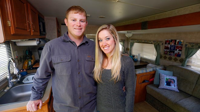 Iowa Cubs pitcher Blake Cooper and his wife, Casey, stand in their 2006 27-foot Fleetwood Mallard, which they've parked at the Adventureland campground during the Pacific Coast League season.